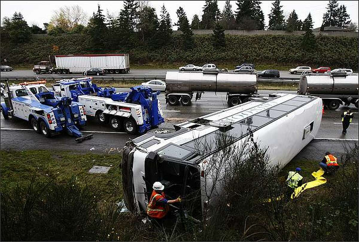 A charter bus lies on its side after overturning on Interstate 5 near Exit 149 Friday morning. The bus was transporting the Bellevue High School football team to a playoff game in Tacoma. Some of the 38 players on board were injured, and the wreck caused a huge traffic jam.