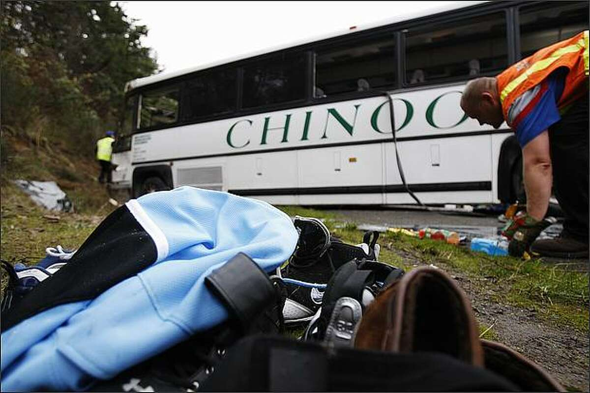 Some personal belongings of Bellevue football players are stacked in front of a Chinook charter bus that was carrying the team to a playoff game when it overturned on Interstate 5 Friday morning.