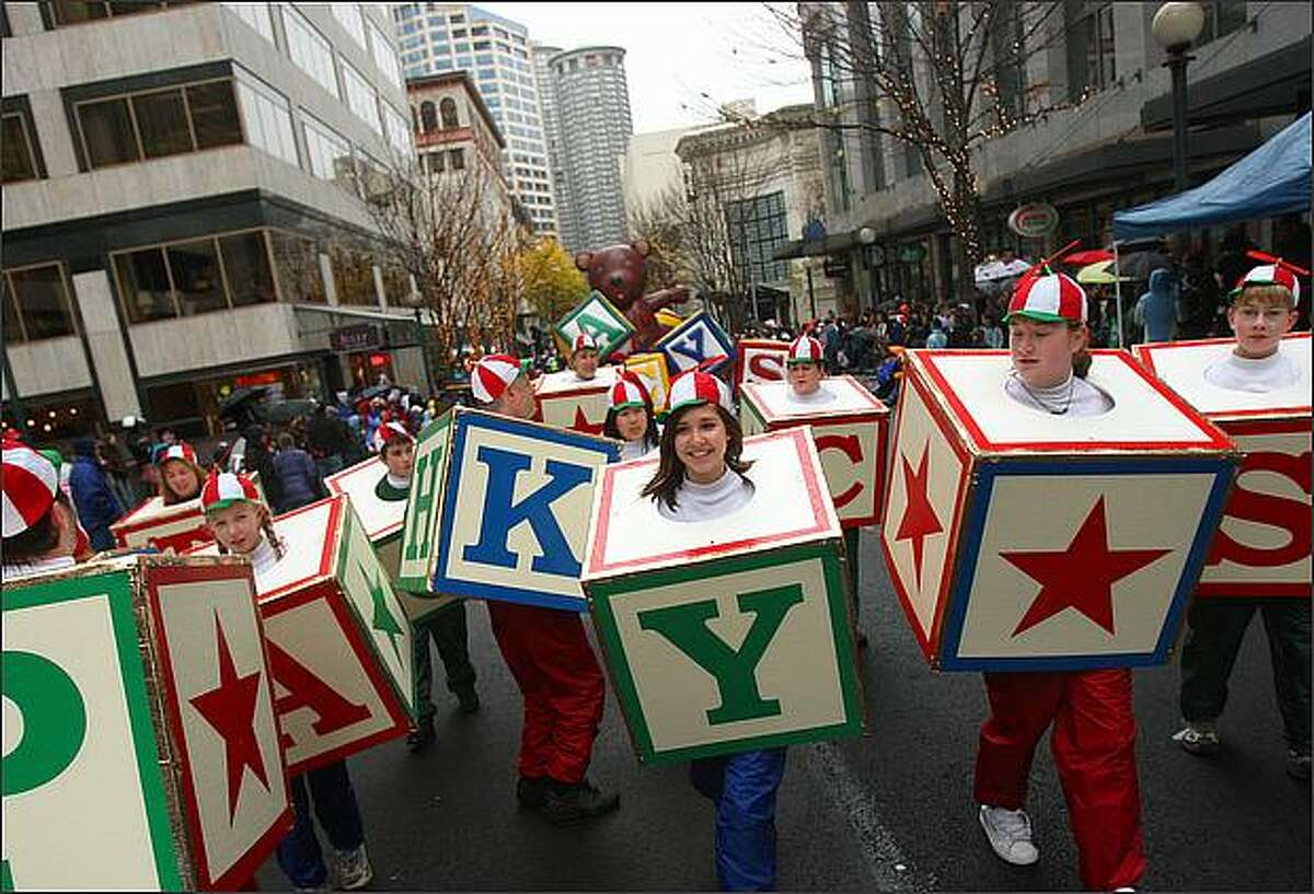 Parade marchers costumed as toy blocks participate in Seattle's annual Macy's Holiday in downtown.