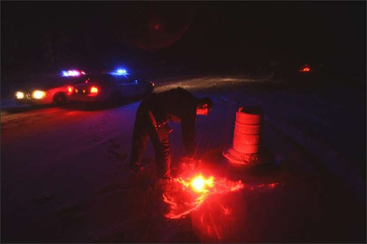 A Washington State Patrolman lights flares to close I-90 at Snoqualmie Pass on Jan. 4, 2009.