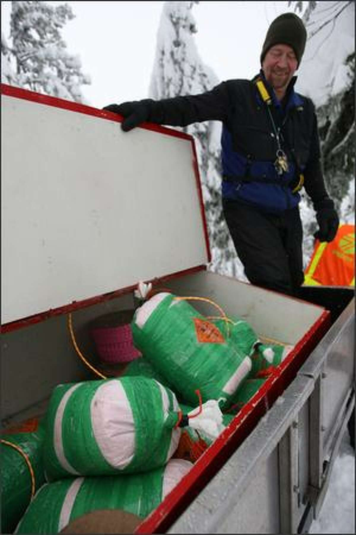 Washington Department of Transportation avalanche forecaster and controller Lee Redden looks over a load of packed explosives to be used to trigger a controlled avalanche at Snoqualmie Pass on Monday, Jan. 5, 2009.