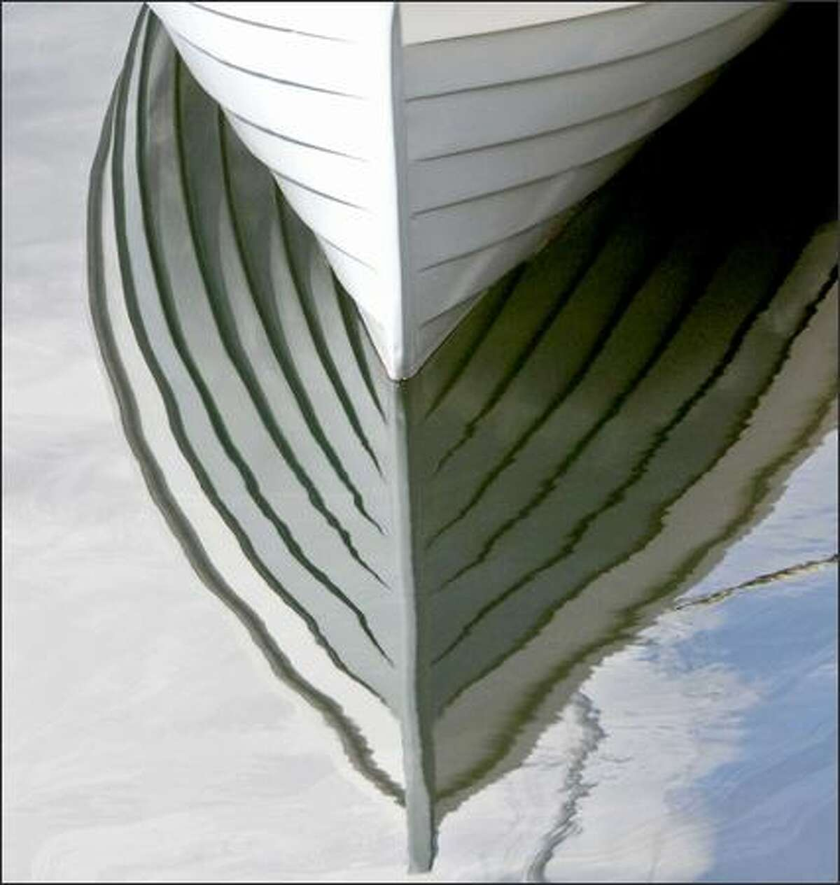 The lines of a Lake Oswego Boat are reflected in the water at the Center for Wooden Boats.