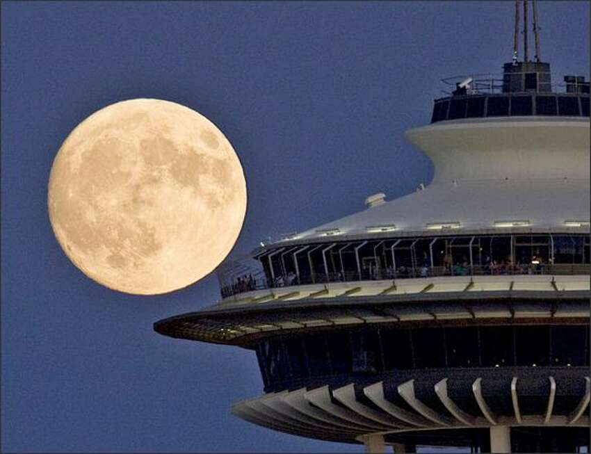 Visitors to the Space Needle enjoy a full moon.Haller: I always find it a challenge to capture a view of the full moon that interests me. Often when I see a full moon start to rise over the Cascade Mountain range, I take off trying to come up with an angle to show something different. Rushing around trying to find something new is a challenge. Once I rushed to Harbor Avenue to make a picture of the moon coming up over downtown buildings, only to have it come up over Beacon Hill. Then rushing around trying to get into a position where a plane taking off from Sea-Tac would pass in front of the moon. The next full moon rise I made a photo of the moon coming up on the left side of a building. A little later that night, I found out that there was another P-I photographer making a photo of the moon coming up on the right side of the building. He was just down the street. Neither one of us knew the other was out shooting the moon.