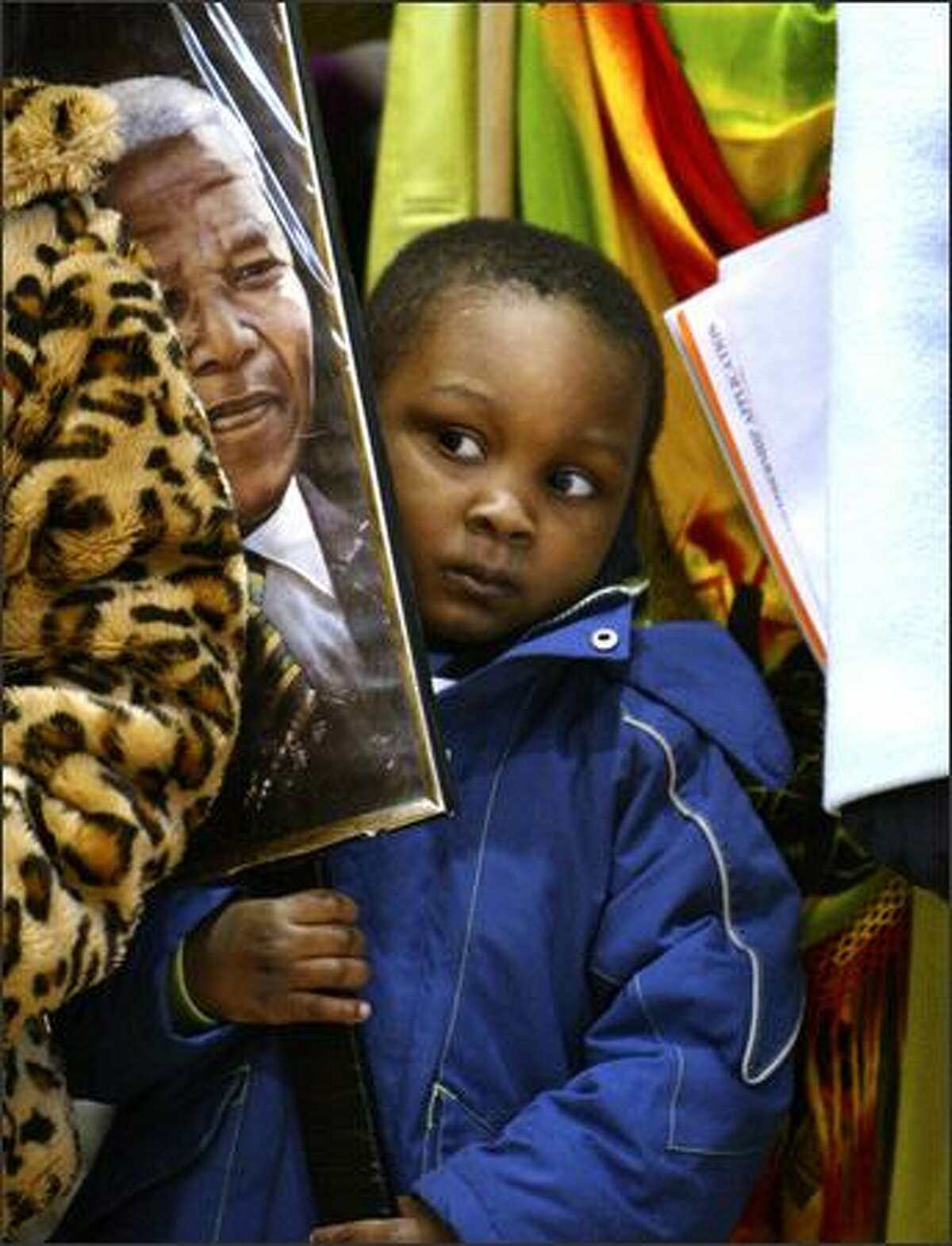 Davon Fuller holds a photo of Nelson Mandela as he squeezes in between his grandmother and older sister at the Franklin High School gym during the annual Martin Luther King Jr. Day celebration and march.Arias: Davon was just one of the hundreds who attended and later participated in the three-mile march that started at the high school and ended at Martin Luther King Jr. Park.
