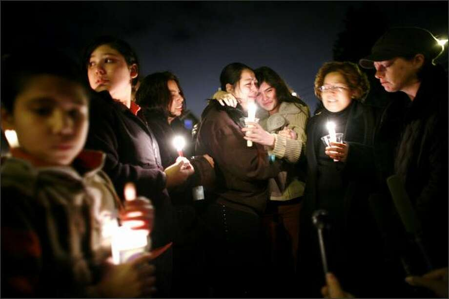 """Karina Blanco Lopez, 15, center right, and her aunt Rosalba Naranjo, center left, gather in front of the home where Noemi Lopez, Karina's mother, was found stabbed to death. Noemi's ex-husband and Karina's father, Jose Angel Blanco, was charged with first-degree murder.Trujillo: Photographing an emotion-filled memorial is uncomfortable and awkward, at best. I was kneeling, trying to keep a low profile, surrounded by tears and raw emotion -- and I felt horrible documenting the pain of those involved. But I also believe that society only confronts problems collectively when we all experience part of the pain. Even if just via a still image.  A neighbor later thanked me for my """"graceful handling of a very difficult situation."""" Photo: Joshua Trujillo, Seattlepi.com"""
