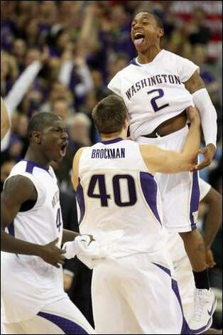 From left, Washington's Darnell Gant, Jon Brockman and Isaiah Thomas celebrate after the final buzzer. Photo: Kevin P. Casey/Associated Press