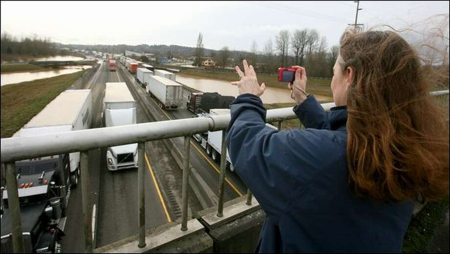 Melissa Sikel of Centralia waves and takes photos of passing trucks as a 20-mile stretch of I-5 reopened. Photo: Scott Eklund/Seattle Post-Intelligencer