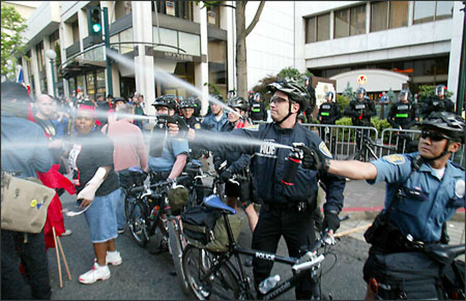 Police spray pepper spray into a crowd during a demonstration last night outside the Red Lion Hotel, site of a police intelligence-training seminar. Photo: Mike Urban, Seattle Post-Intelligencer