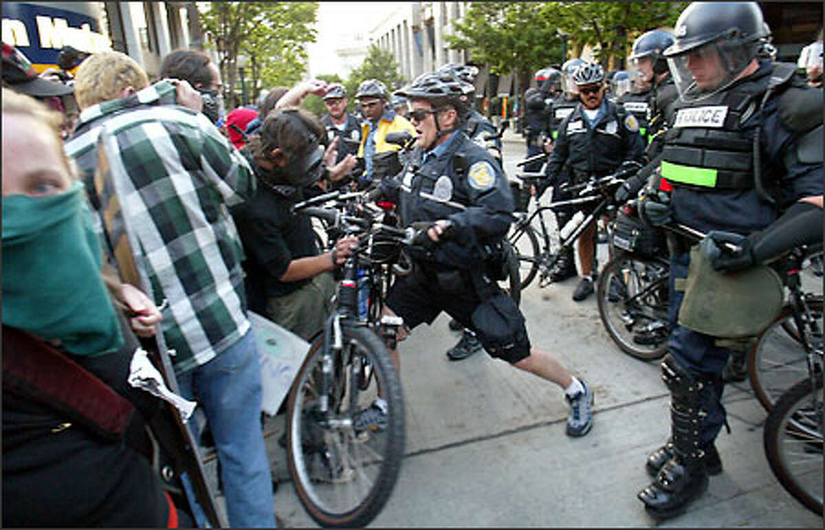 An officer from the Seattle Police Department shoves his bike into a crowd during a demonstartion outside the Red Lion Hotel.