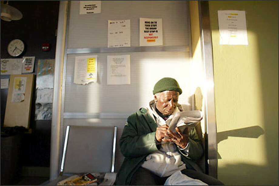 John, who didn't give his last name, works a crossword puzzle while waiting his turn for the showers. Photo: Mike Urban, Seattle Post-Intelligencer
