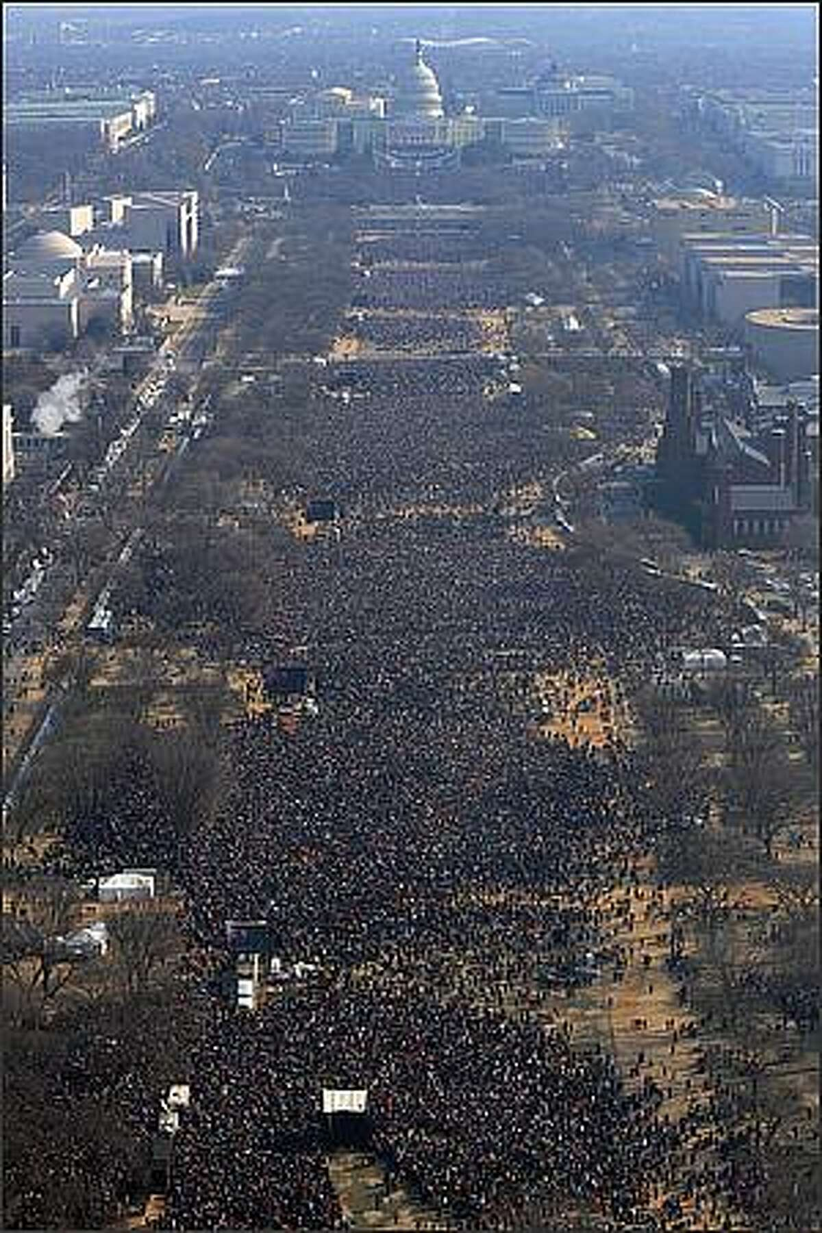 People gather on the National Mall in Washington, DC, to watch the inauguration of US President-elect Barack Obama as 44th US president. JEWEL SAMAD/AFP/Getty Images