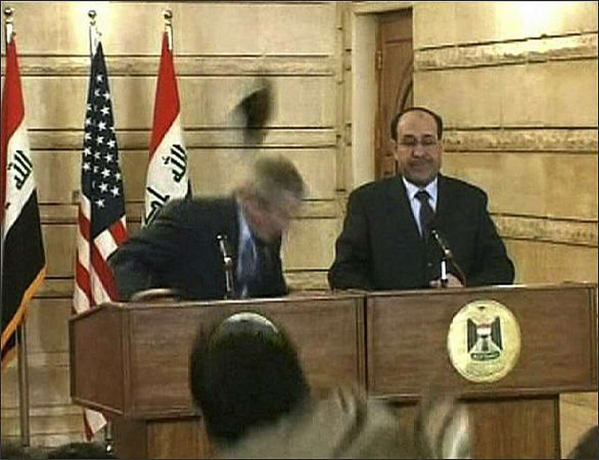 In this image from APTN video, a man throws a shoe at President George W. Bush during a news conference with Iraq Prime Minister Nouri al-Maliki in Baghdad. The man threw two shoes at Bush, one after another. Bush ducked both throws, and neither man was hit. (AP Photo/APTN)