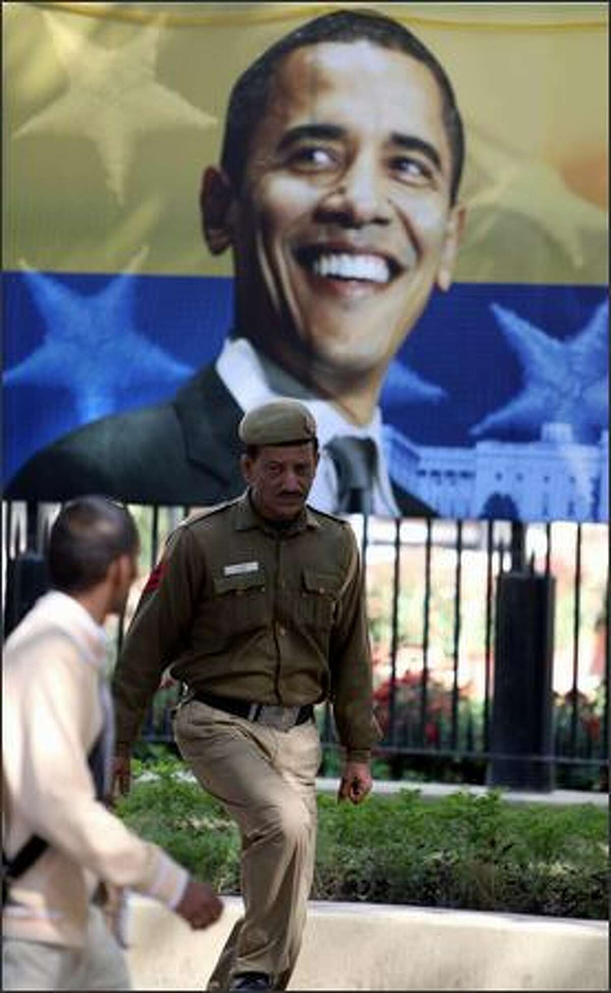 A police-man stands guard outside the American centre in front of a poster of US President-elect in New Delhi on Tuesday.