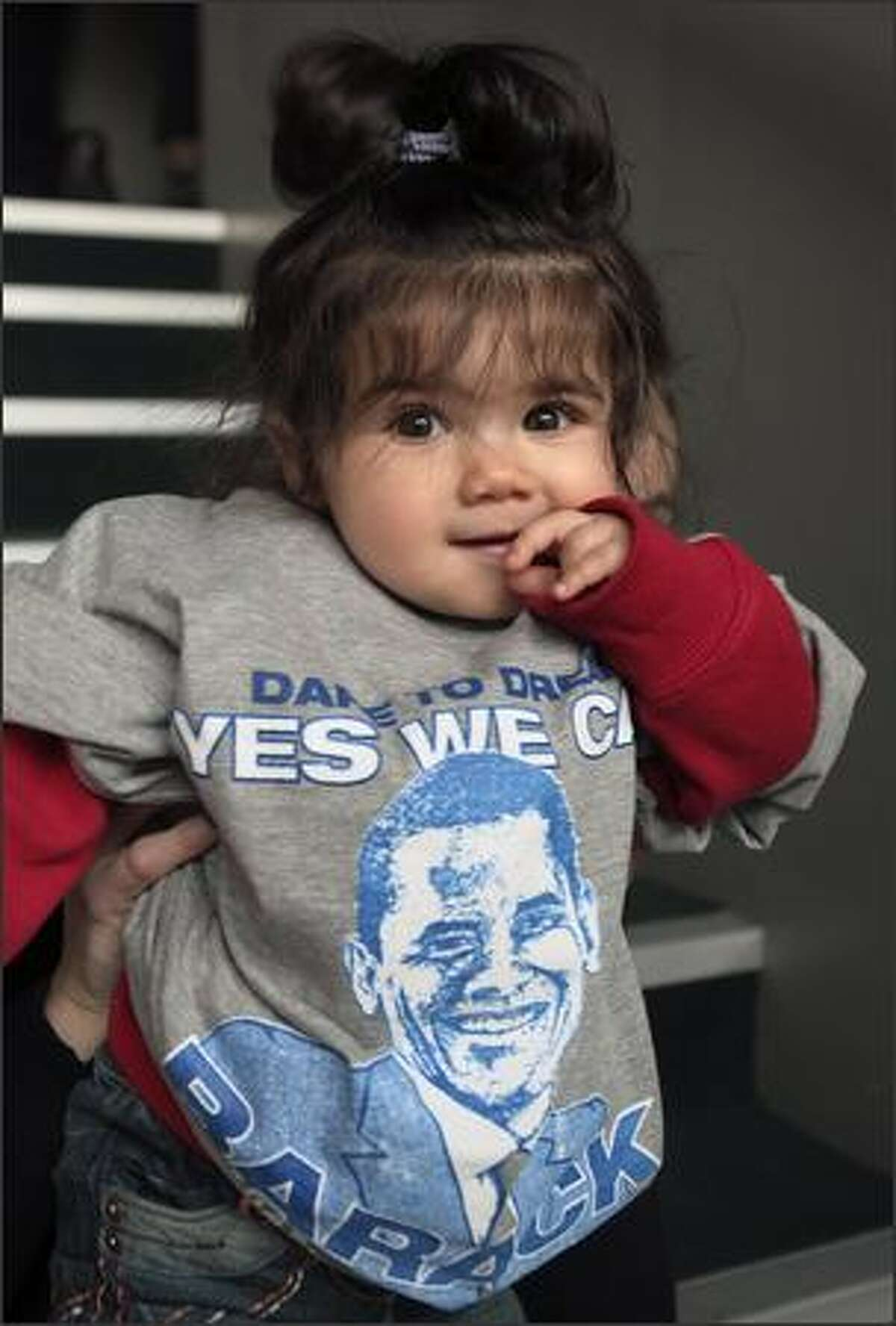 A young girl wears a Barack Obama shirt at the Bernie Grant Arts Centre in Tottenham, London, as people gather to watch a live broadcast of the inauguration of U.S. President Barack Obama, on Tuesday. Hundreds of thousands of people streamed into Washington Tuesday to witness the inauguration of Barack Obama as the first black U.S. president, in a moment of national unity after years of political tumult.