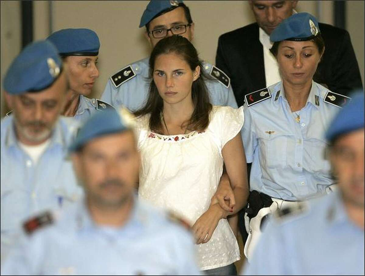 American murder suspect Amanda Knox, center, is escorted by Italian police officers from Perugia's court after a hearing in central Italy last September. Knox, along with her former Italian boyfriend, Raffaele Sollecito, and Rudy Hermann Guede, are suspects in the November 2007 slaying of British exchange student Meredith Kercher.