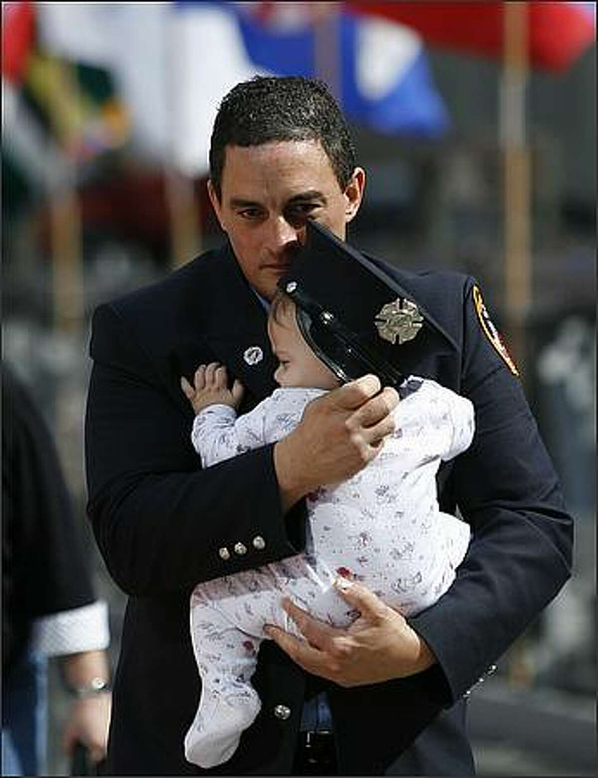 A firefighter holds a child as he walks from the World Trade Center after paying their respects during the seventh annual 9/11 commemoration ceremony held at Ground Zero September 11, 2008 in New York City. Family and friends of the victims, heads of government and others gathered at the annual ceremony to remember the attacks that killed more than 2,700 people with the destruction of the World Trade Center on September 11, 2001. (Photo by Shannon Stapleton-Pool/Getty Images)