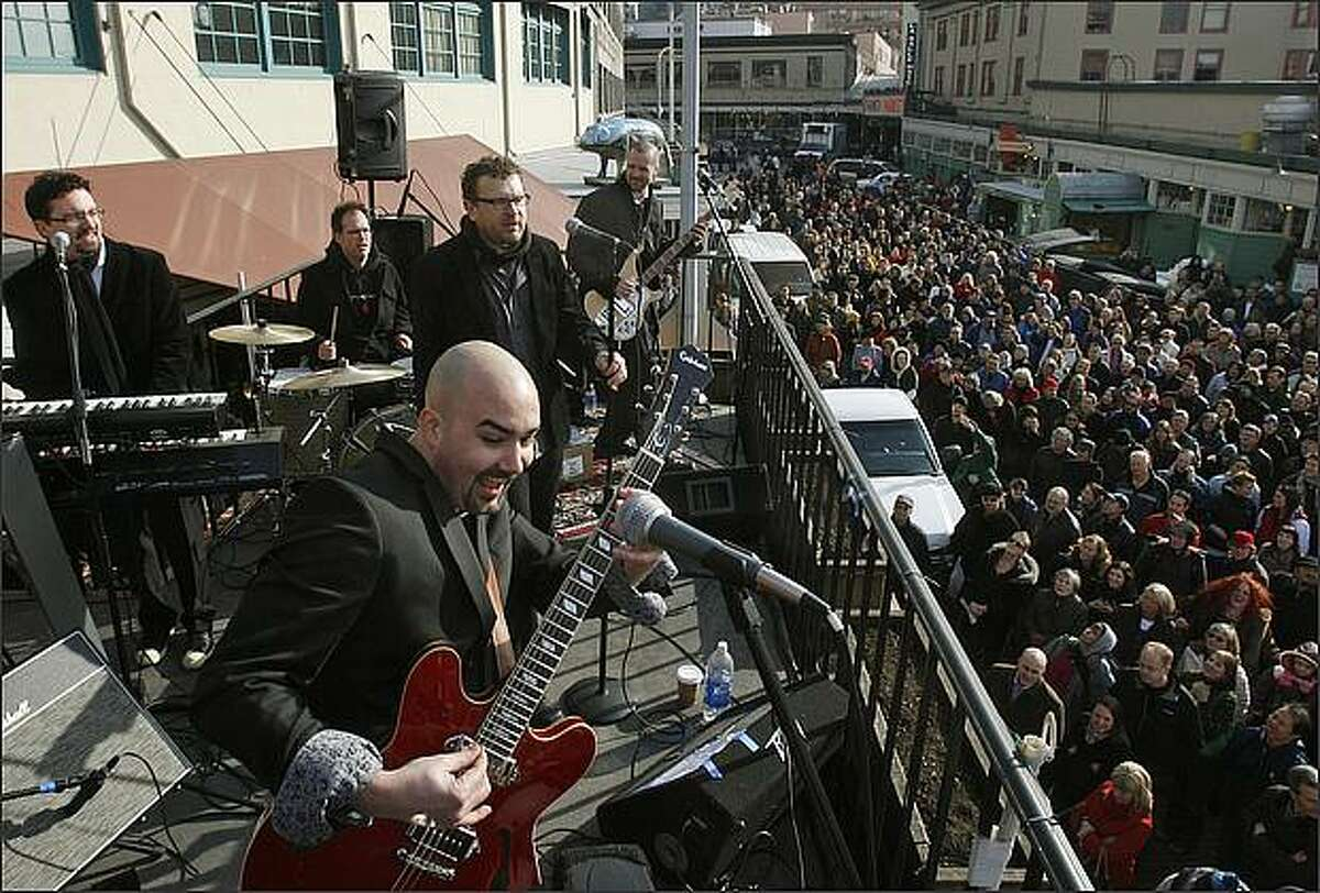 Beatles cover band Creme Tangerine, including guitarist Tim Mushen, performs on the balcony of the Copacabana Cafe in the Pike Place Market in Seattle. The concert was a tribute to the 40th anniversary of the The Beatles' last performance, famously known as
