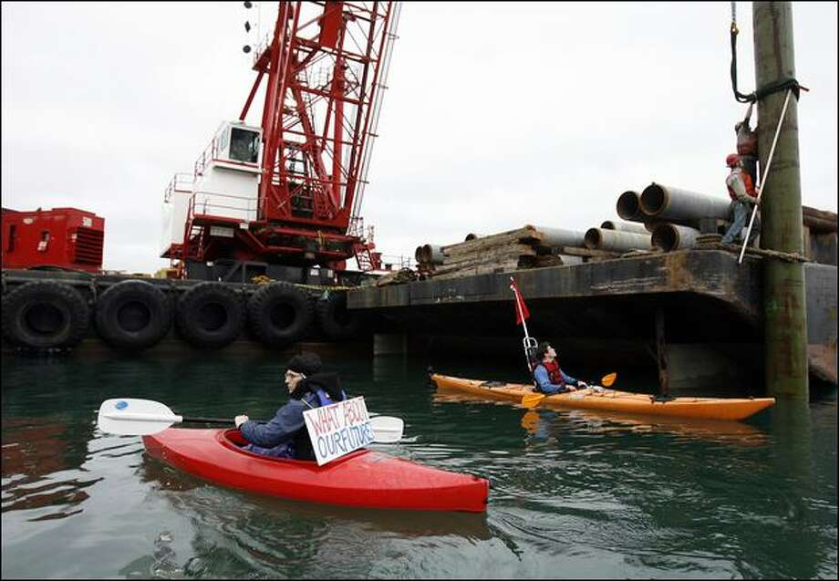 Ignoring a 100-foot restricted zone around the barge, protesters Swaneagle, left, and Logan Price try to disrupt work on a Glacier Northwest gravel mine dock off Maury Island on Tuesday. The dockworkers were securing a 120-foot piling to a construction barge. Photo: Mike Urban/Seattle Post-Intelligencer