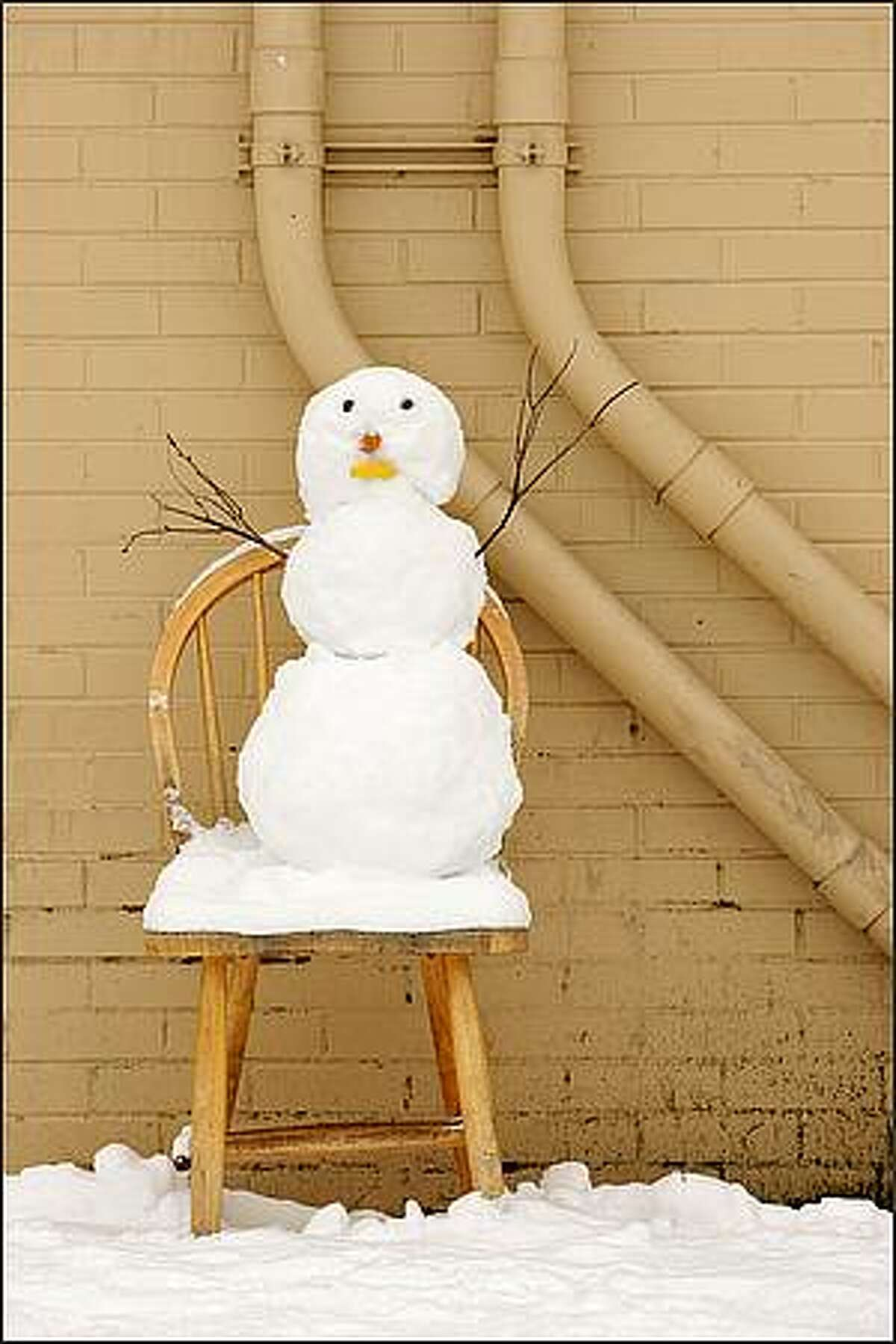 A small snowman takes a load off in the Wallingford neighborhood of Seattle.