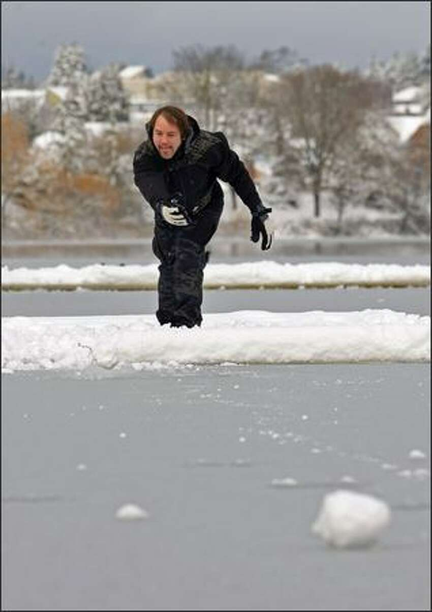Scott Smith of Seattle lets another snowball roll onto the frozen water while