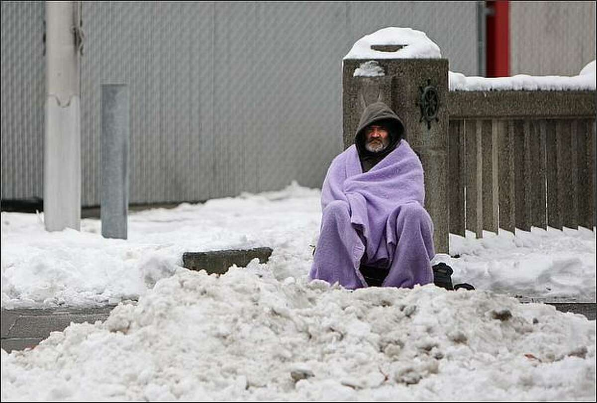 A homeless man, who would not give his name, sits on Alaskan Way in downtown Seattle. The man said that he has been sleeping near the viaduct and is thankful that warmer weather should be coming. Dec. 23, 2008.
