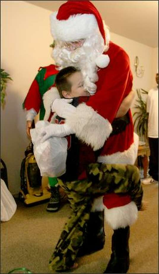 Although tenative at first, Aaron, 7, warmed up to Santa with the Forgotten Children's Fund as he gives him a big hug at his apartment in Seattle. Photo: Scott Eklund, Seattle Post-Intelligencer
