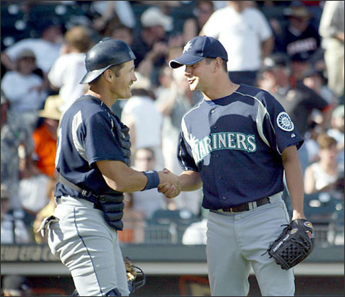 Catcher Pat Borders congratulates Brian Sweeney after the reliever closed out Seattle's victory.