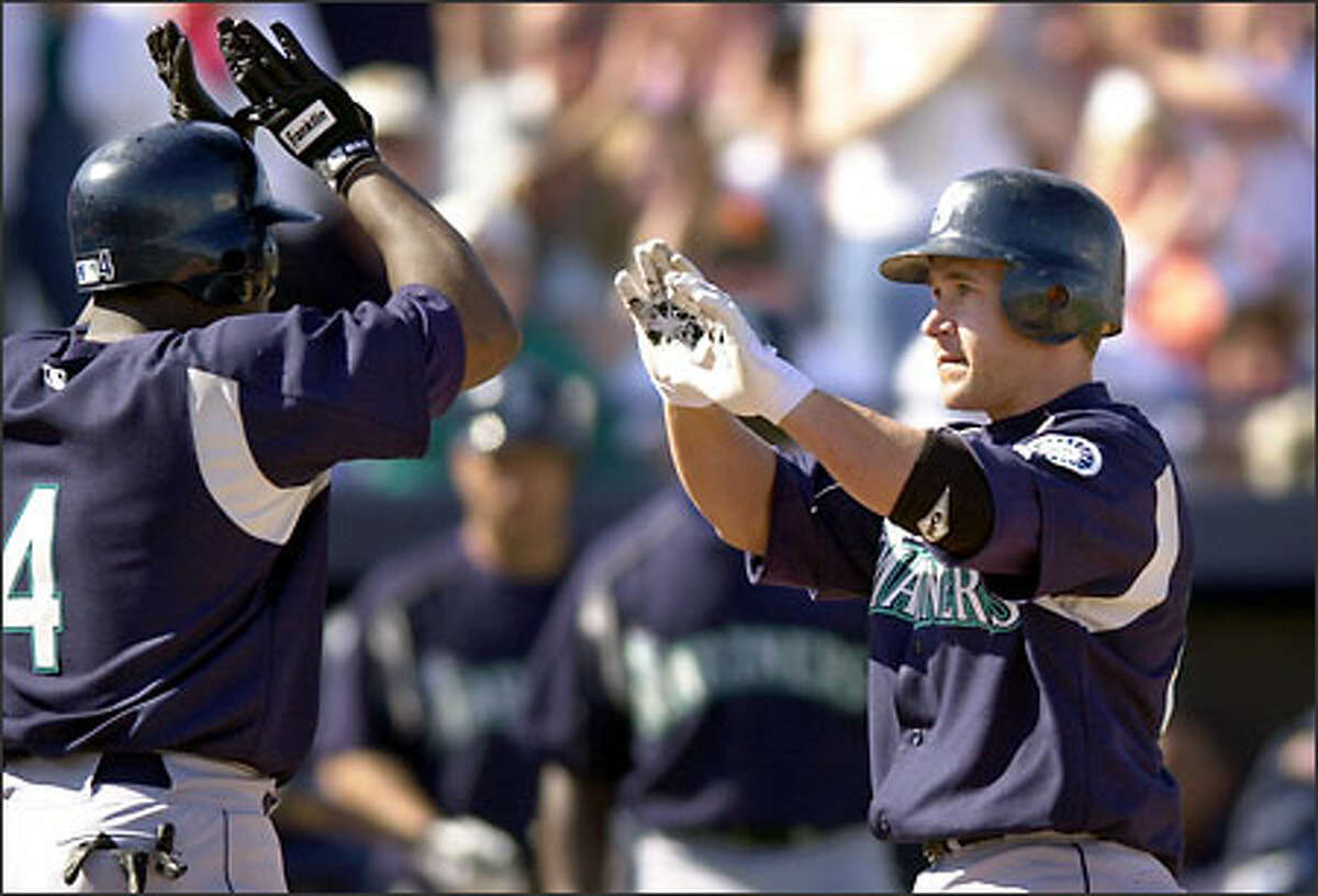 Seattle Mariners' Bret Boone, right, is met at the plate by Mark McLemore following his fourth-inning home run in an exhibition game against the San Diego Padres, Sunday, March 2, 2003, in Peoria, Ariz. McLemore also scored on the play.