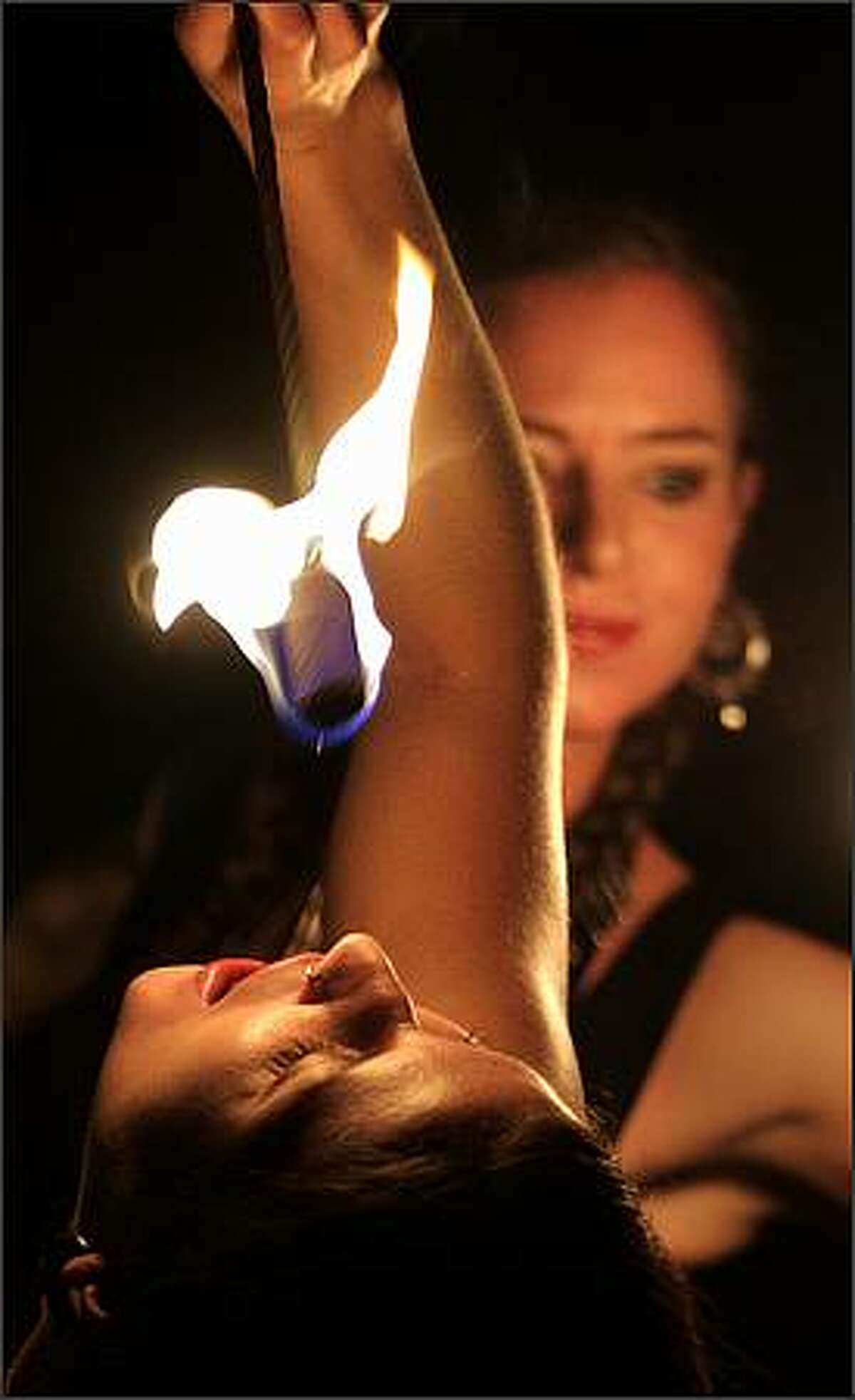 Elizabeth Indigo prepares to swallow fire while performing with Kim Brown and the rest of Pyrosutra Incendiary Dance at McCaw Lecture Hall in Seattle. Dec. 5, 2008