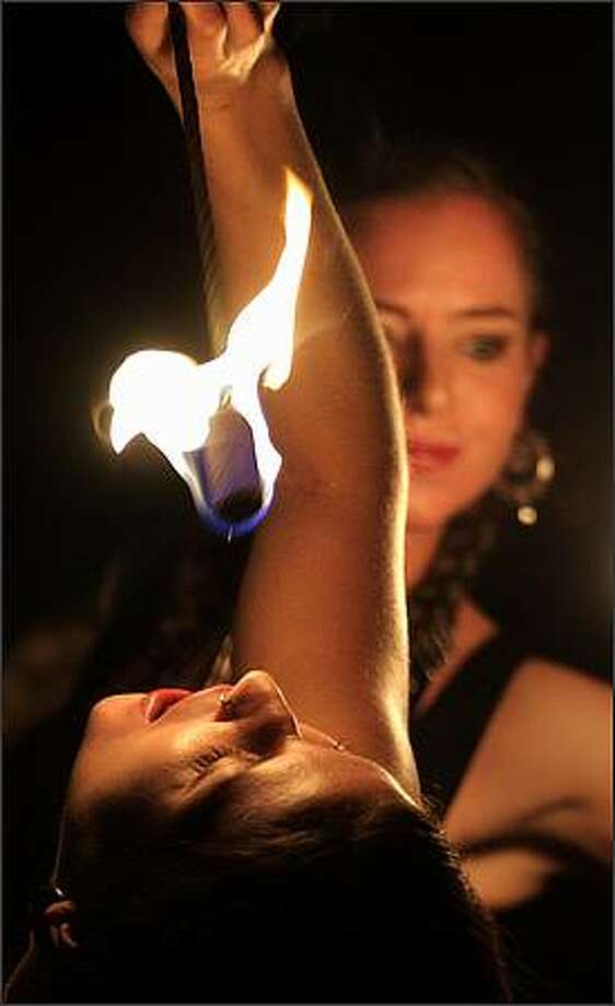 Elizabeth Indigo prepares to swallow fire while performing with Kim Brown and the rest of Pyrosutra Incendiary Dance at McCaw Lecture Hall in Seattle. Dec. 5, 2008 Photo: Andy Rogers, Seattle Post-Intelligencer