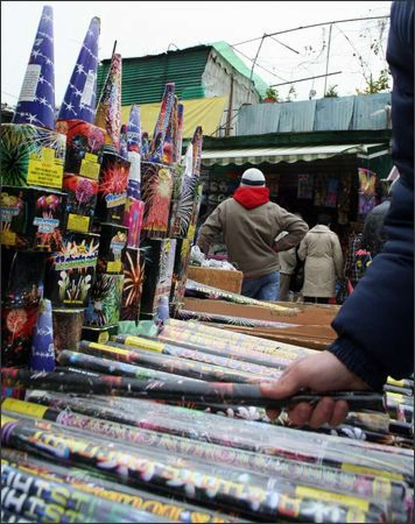 Albanians buys Chinese-made fireworks at a popular street market in Tirana, on December 31, 2008. Fireworks are the most sold items in the market around the New Year's Eve but also a nightmare for policemen and emergency doctors that deal every year with the casualties of the festivities. AFP PHOTO / GENT SHKULLAKU