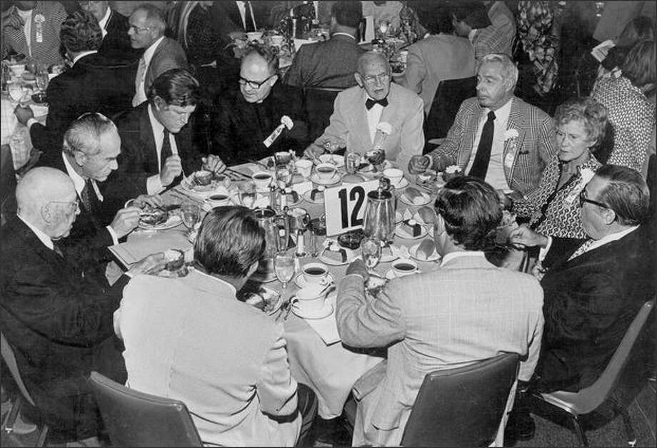 Brougham holds court at the 1975 dedication of the Fred Hutchinson Cancer Research Center. From lower left: Henry Broderick, Dr. Bill Hutchinson, Sen. Edward Kennedy, Archbishop Raymond Hunthausen, Brougham, Joe DiMaggio, Patsy Hutchinson, Sen. Warren Magnuson, Gov. Dan Evans, and Ritter Collett.
