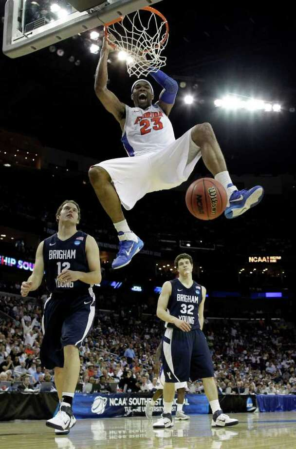 Florida's Alex Tyus (23) dunks in front of BYU's Jimmer Fredette (32) and Logan Magnusson (12) during overtime of the NCAA Southeast regional college basketball semifinal game Thursday, March 24, 2011, in New Orleans. Photo: David J. Phillip