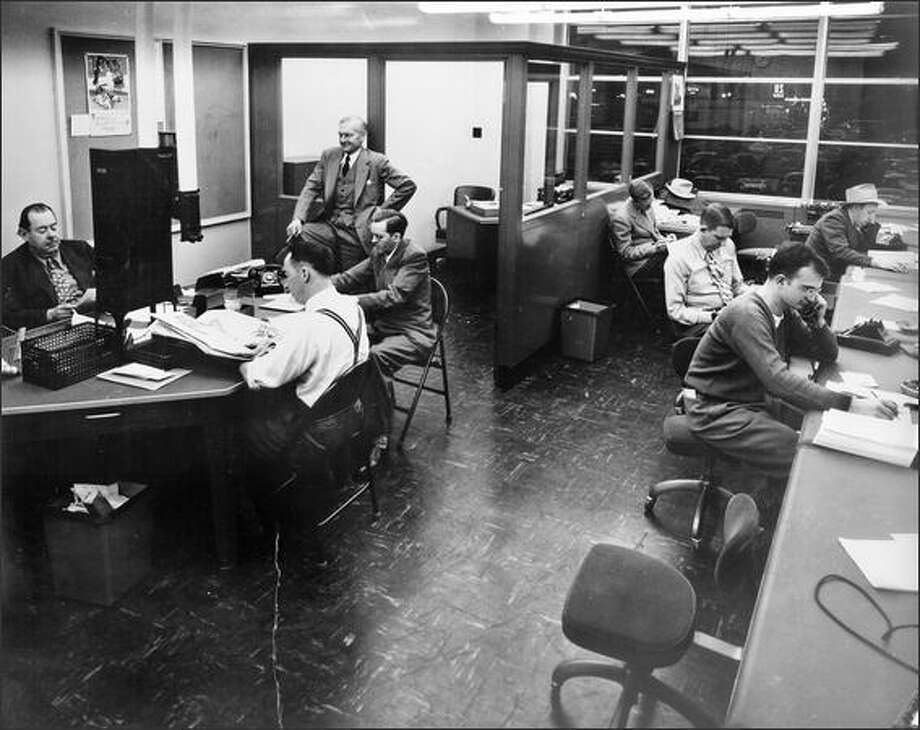 Royal Brougham, standing upper left, and sports writers in the P-I newsroom.