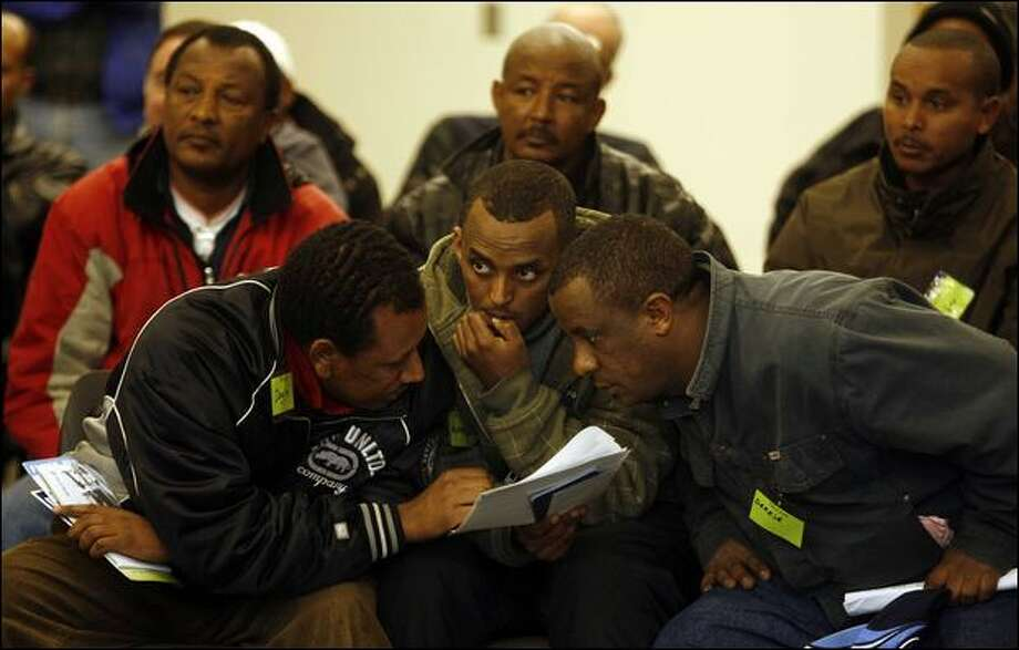 From left, Dagim Mengistu, Asmamaw Mijena and Dereje Muhamed huddle Wednesday night to discuss the Port of Seattle's proposed truck emission standards set forth in a meeting with drivers. Photo: Mike Urban/Seattle Post-Intelligencer