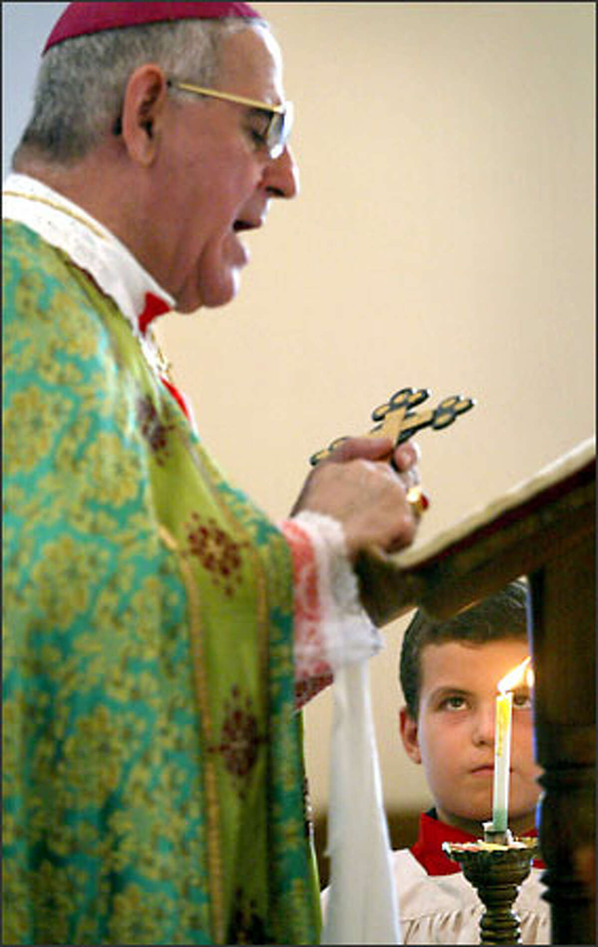 Altar boy Farj Khaleed, 11, assists Archbishop Djibrael Kassab during Mass in Basra. When war broke out in Basra, most Christians left the city, as they did in the first Gulf War. Only now some of them are returning, Kassab said.