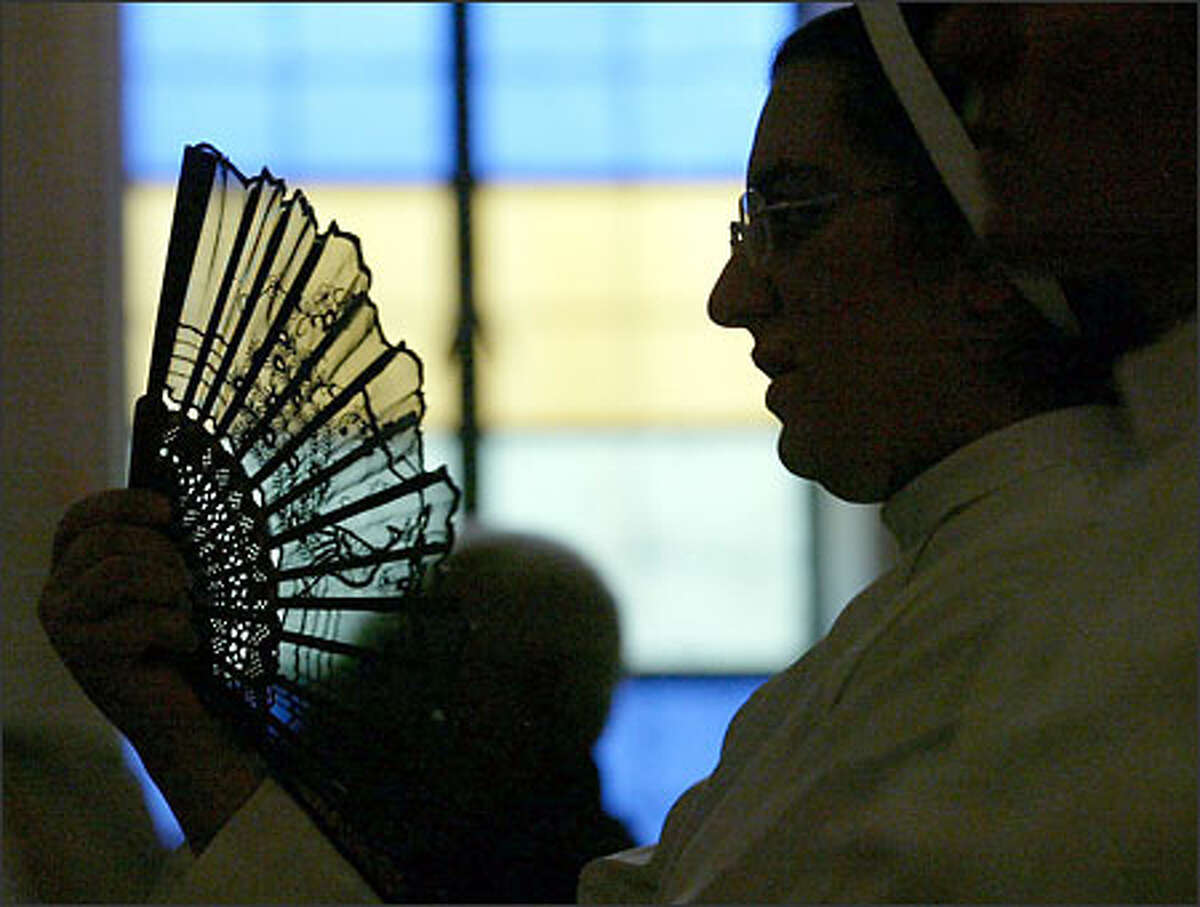During one of several power outages during mass, Sister Intiqal Ramzi cools herself. Before the war, parishioners said the outages rarely happened during service.