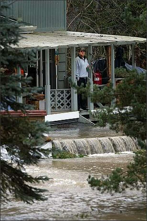 A man who did not want rescue crews to help him stands on porch despite a raging Cedar River which crested and flowed all around him, in Maple Valley, Wash. Photo: Karen Ducey, Seattle Post-Intelligencer