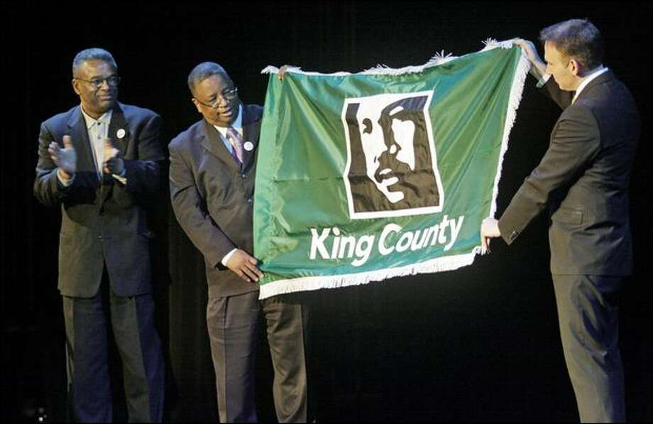 From left, King County Executive Ron Sims, King County Councilman Larry Gossett and King County Council Chairman Dow Constantine unveil the new county flag during the 22nd annual Dr. Martin Luther King Jr. Celebration at the Paramount Theatre in Seattle on Thursday. Photo: Dan DeLong/Seattle Post-Intelligencer