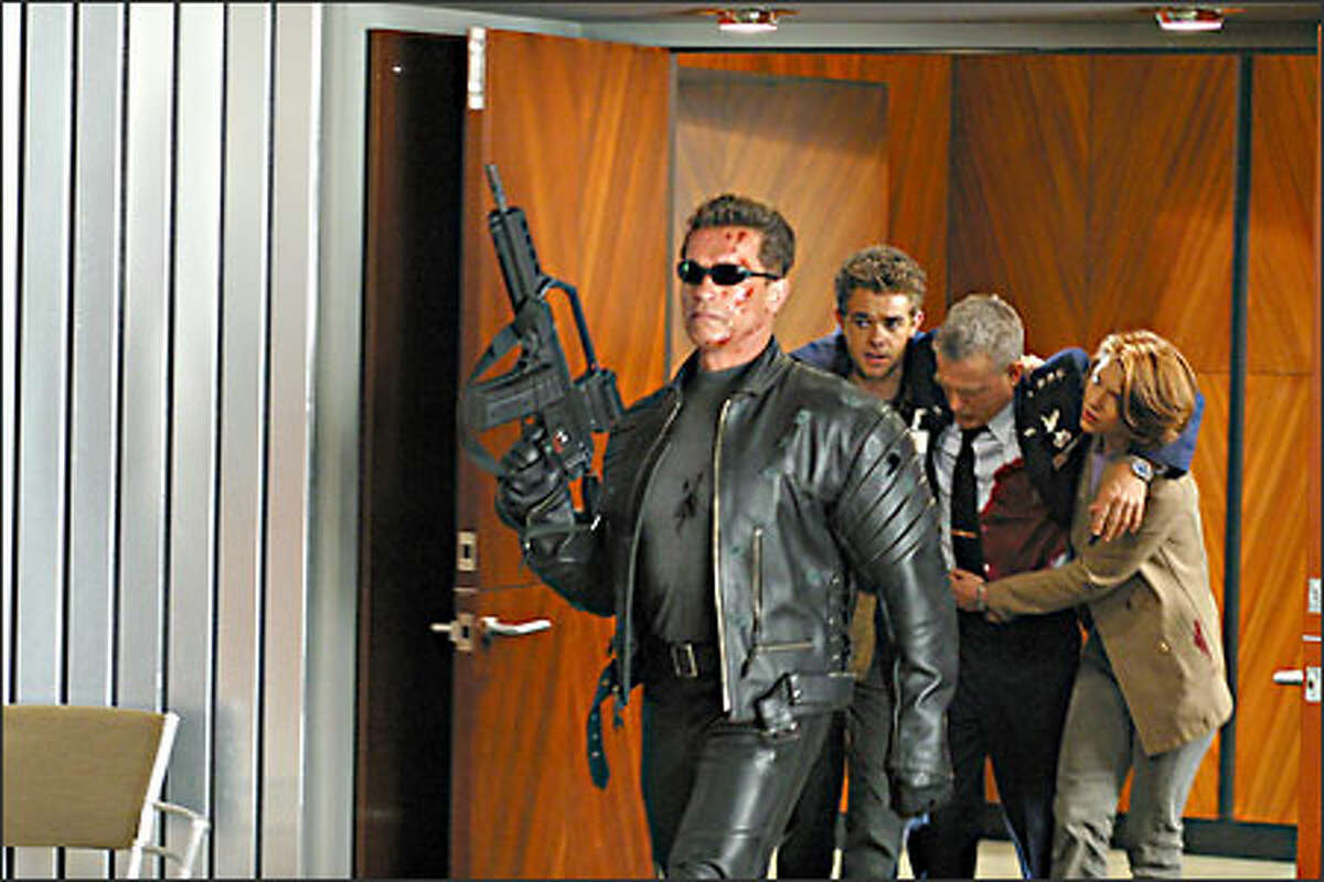 The Terminator (Arnold Schwarzenegger) takes point as John (Nick Stahl) and Kate (Claire Danes) help Robert Brewster (David Andrews).
