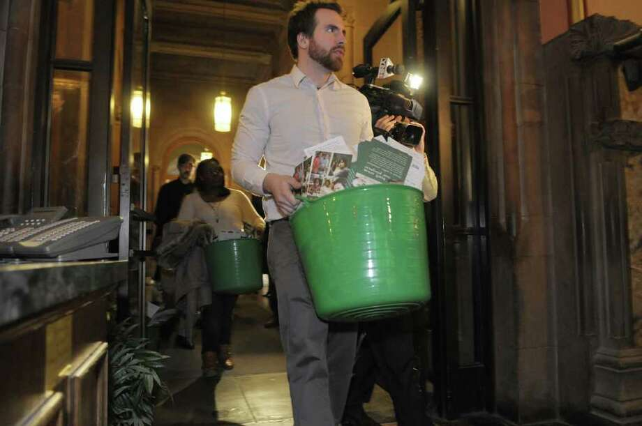 Harrison Watkins, a communications associate with the Alliance for Quality Education, carries in a bucket of postcards as the cards were delivered to Governor Cuomo's office at the Capitol in Albany, NY on Thursday, March 24, 2011.  The postcards were sent in by New Yorkers who were asking the Governor restore his spending cuts for education.   (Paul Buckowski / Times Union) Photo: Paul Buckowski