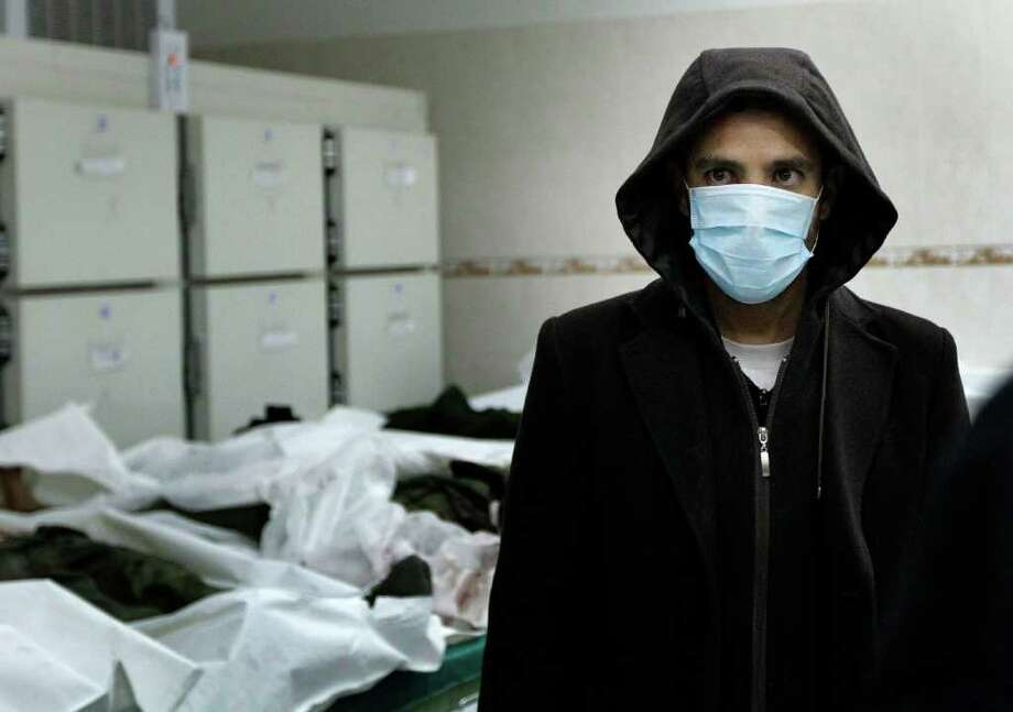 "In this image taken during an organized trip by the Libyan authorities, a morgue employee stands amidst 15 bodies at the morgue in Tripoli, Libya, early Friday, March 25, 2011. Libyan authorities said the corpses were  victims of  alliance bombings 30 hours earlier. Though some markings on  at least two body bags stated ""unidentified"" and the date ""18 March 2011, neither the cause of deaths nor the identities could be independently verified. (AP Photo/Jerome Delay) Photo: Jerome Delay"
