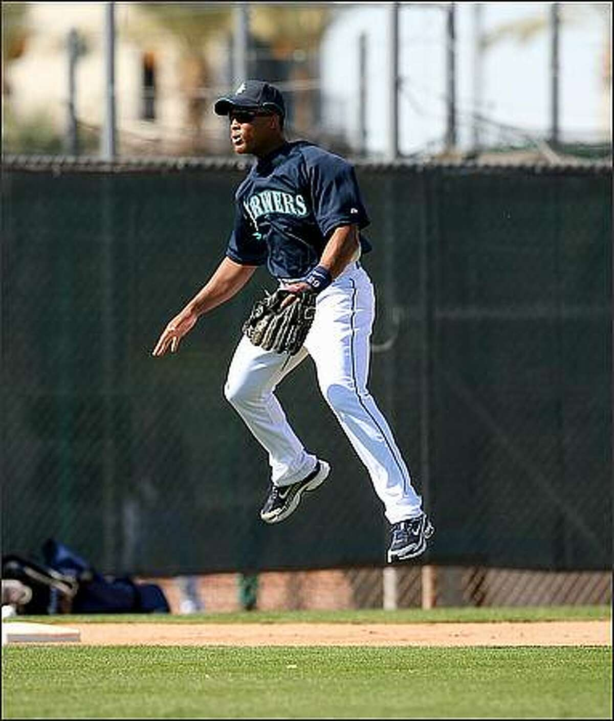 Third baseman Adrian Beltre gets some air as an unseen ground ball gets his attention during batting practice.