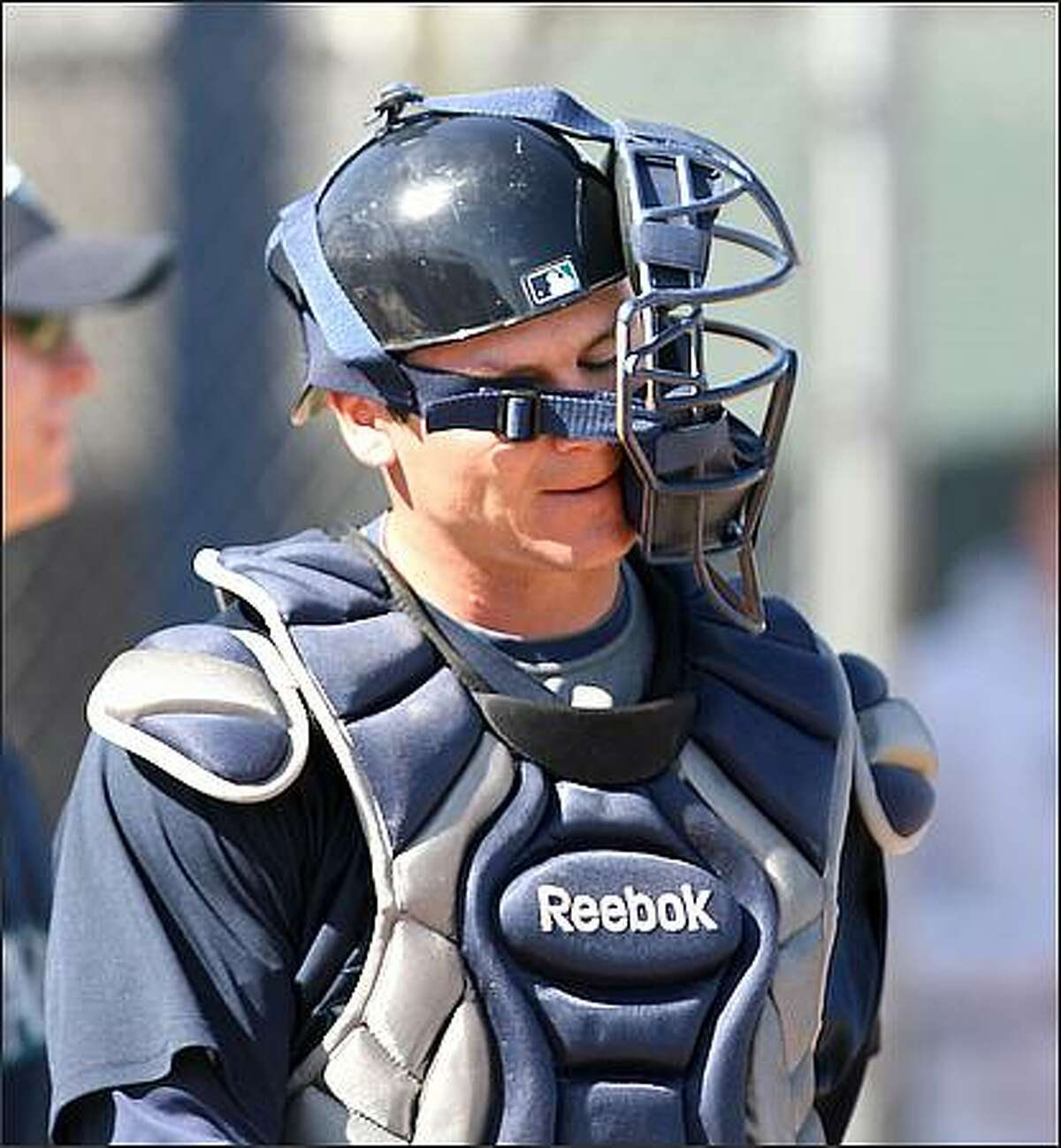 Catcher Rob Johnson's mask sits askew after he made a throw to second base during a drill at the Seattle Mariners spring training facility in Peoria, Ariz.