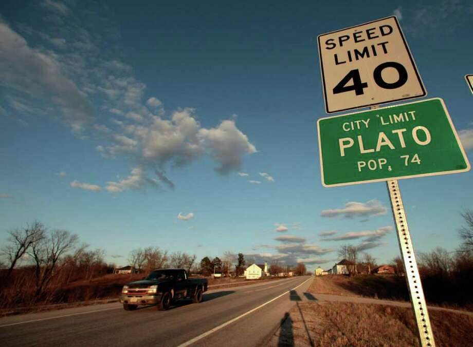 A car drives through Plato, Mo., which has been designated the population center of the United States according to the 2010 census, Wednesday, March 23, 2011. In a nation of nearly 310 million people, America's population center rests not in the Midwestern skyline of St. Louis or Chicago, but in a tiny village in southern Missouri with a population of 109. The announcement by the Census Bureau shifts the location about 30 miles southwest since 2000, but it signifies larger trends: America's population is marching westward from the Midwest, pulled by migration to the Sun Belt. And in a surprising show of growth, Hispanics now account for more than half of the U.S. population increase over the last decade. (AP Photo/Charlie Riedel) Photo: Charlie Riedel
