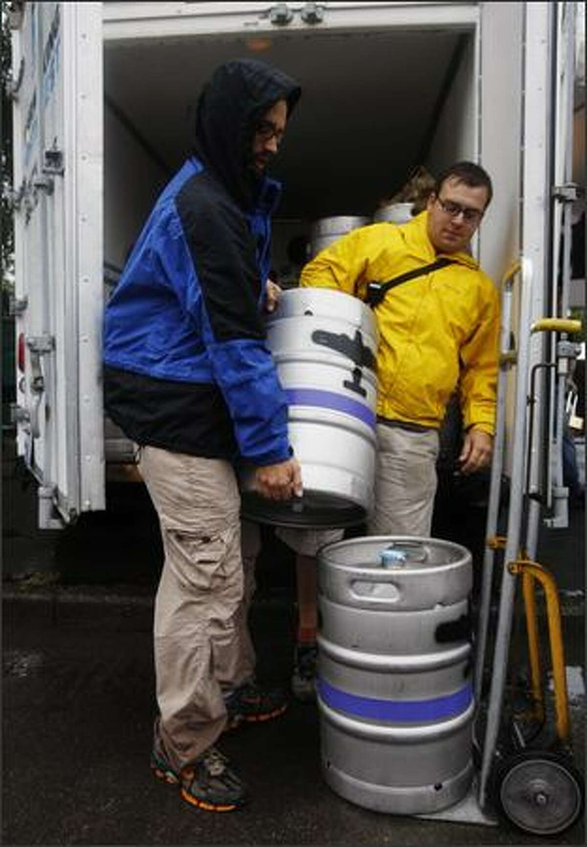 Sean Hunter, left, and Dylan Levalley unload a full keg.