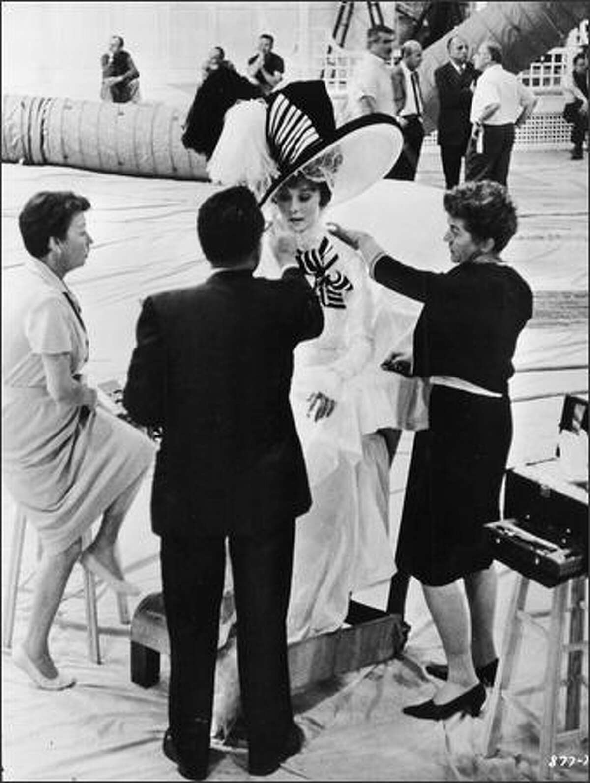 Belgian-born actor Audrey Hepburn (1929-1993) wears an elaborate costume while having her makeup done on the set of 'My Fair Lady,' directed by George Cukor, 1964.