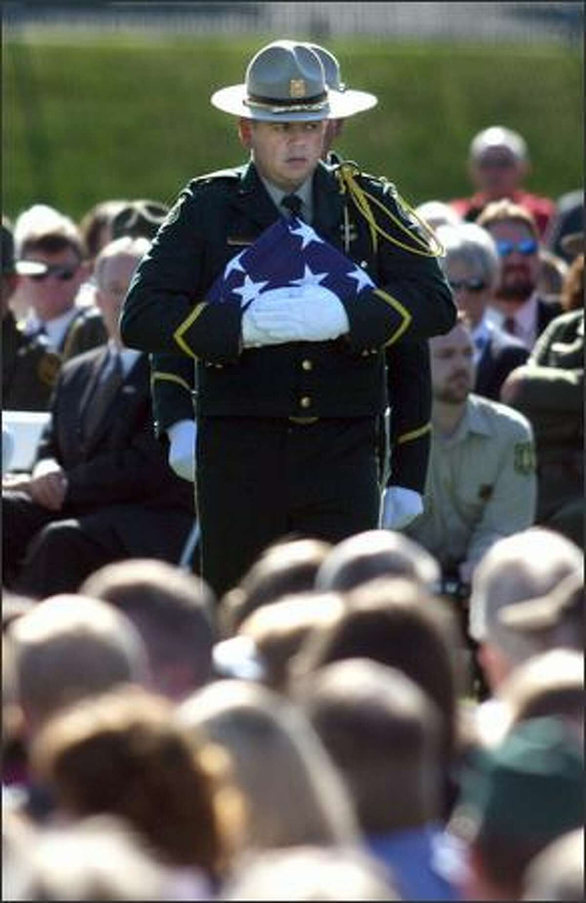 Forest Service officials prepare to unforld, display and refold an American flag to be given to Kristine Fairbanks' daughter, Whitney Fairbanks, during a memorial service for the slain officer in Port Angeles on Monday.
