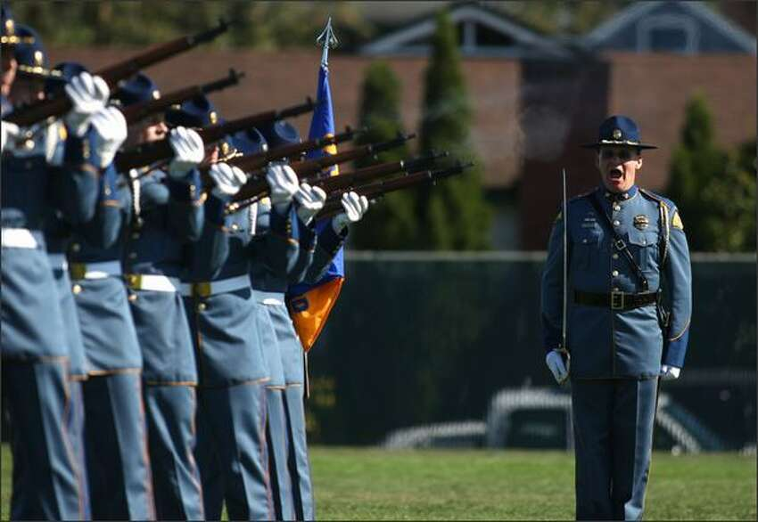 Members of the Washington State Patrol perform a 21-gun salute during a memorial service for Forest Service Officer Kristine Fairbanks at Civic Field in Port Angeles on Monday.