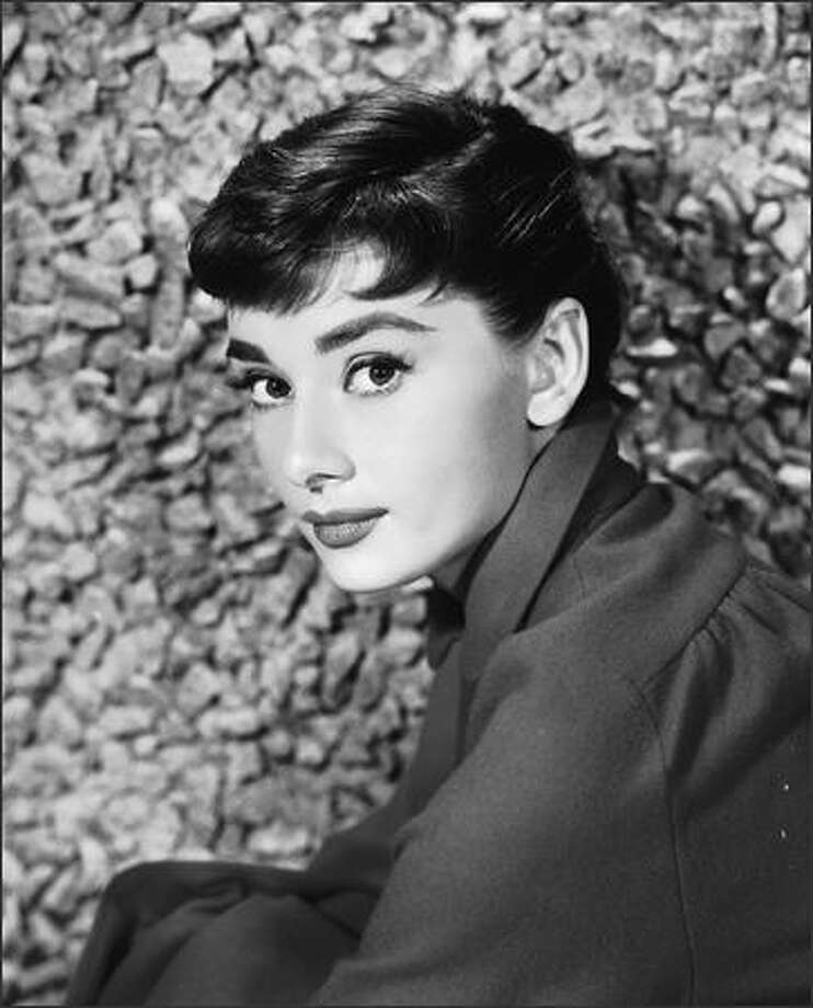 Iconic Audrey Hepburn, sitting by a stone wall in the early 1950s. Photo: Getty Images